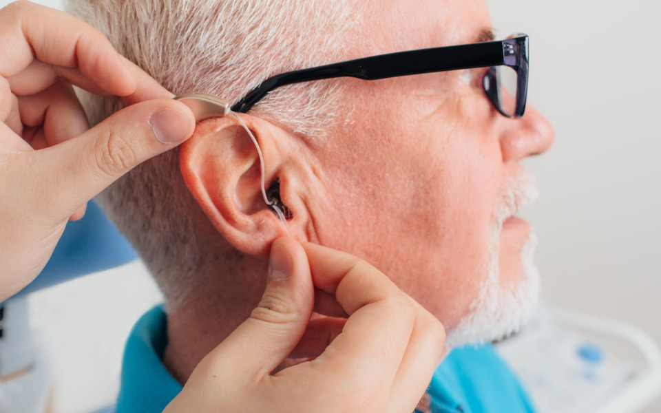 adjusting-of-a-hearing-aid-for-an-aged-man-picture-id1007426094